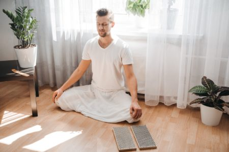 Young man meditating on his living room on the floor, sitting in the lotus position with closed eyes