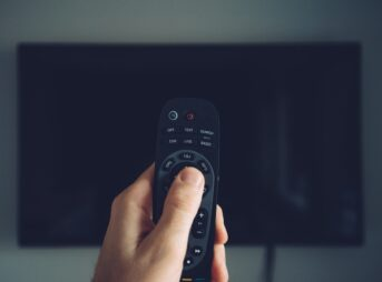 Male hand with TV remote controller